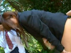 Two sexy schoolgirls are sharing a hard cock outdoors