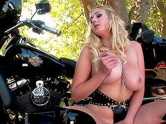 Slender blonde is posing on the bike
