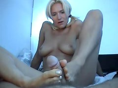 Slim chick in pigtails gives POV footjob