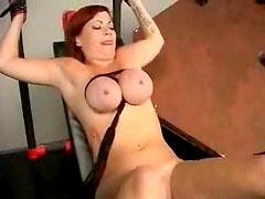 Redhead with big tits tied up in the dungeon