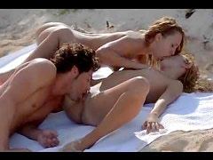 Erotic threesome on a towel at the beach