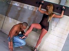 Charming Linda Ray is giving black stud a lusty foot job despite being chained to the wall
