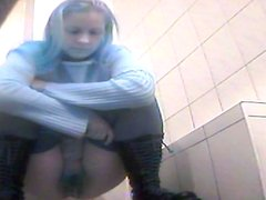 Blonde is sitting in pissing in the hole