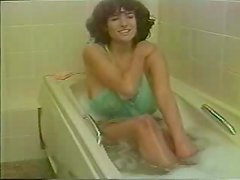 Busty brown-haired milf plays with her big boobs in a bathroom