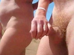 Chubby chick pleases some guy with a handjob on a beach