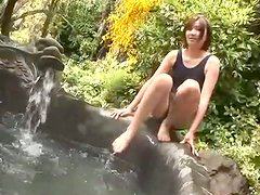 Brownhead Japanese girl is bathing in a pool outdoor