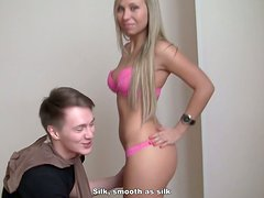 Russian slut in pink lingerie kneels down to blowjob two dicks at a time